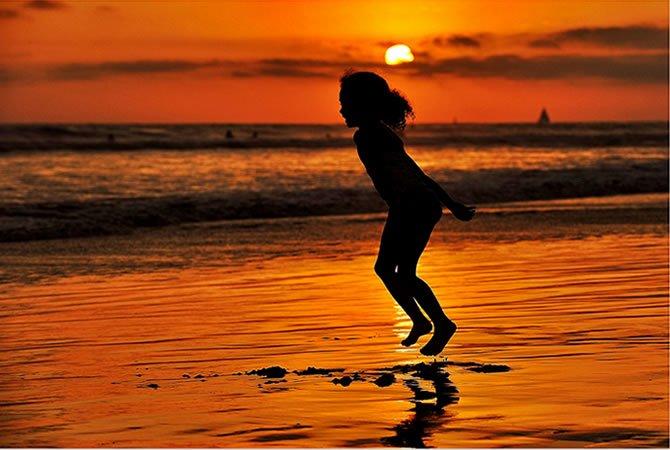 Girl Jumping for Joy at Sunset in Oceanside